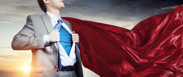 On guardiance of your interests. Young businessman dressed as superhero against cityscape background Stock Photos