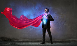 On guardiance of your interests. Young businessman dressed as superhero against concrete background Stock Photo