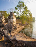 Guardiani di pietra su un ponte all'entrata ad un tempio in Siem Reap, Cambogia Immagine Stock