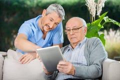 Guardiano che assiste uomo senior nel usando Digital Fotografia Stock Libera da Diritti