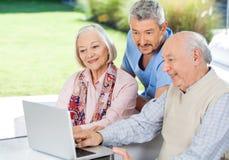 Guardiano che guarda le coppie senior facendo uso del computer portatile Fotografie Stock