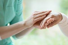 Guardiano che massaggia la mano del ` s del pensionato immagine stock