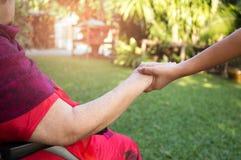 Guardiano che spinge donna senior nella sedia a rotelle fotografia stock libera da diritti