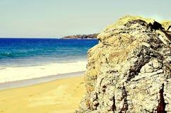 Guardiano della roccia che trascura spiaggia incontaminata Fotografie Stock