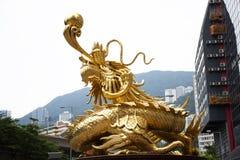 Guardiano dorato del drago della scultura alla rotonda alla strada della collina di Morrison in Hong Kong, Cina immagini stock libere da diritti
