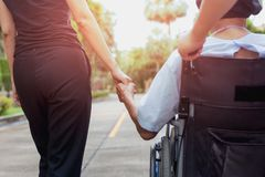 Guardiano e figlia che spendono tempo all'aperto con il paziente in sedia a rotelle immagini stock