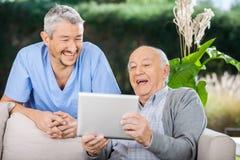 Guardiano maschio ed uomo senior che per mezzo del PC della compressa fotografia stock libera da diritti