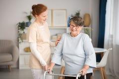 Guardiano medico che aiuta donna senior fotografia stock