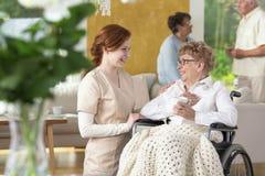 Guardiano tenero che rende ad uno ia anziano della donna una sedia a rotelle ridere i fotografie stock