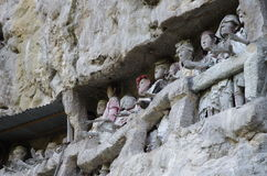 Guardians of graves, figures watching the dead. Carved figures outside of graves in a rocky cliff,  superstition in Toraja, Sulawesi, Indonesia Stock Image