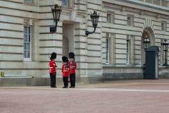 Guardias reales del ` s de la reina de servicio en el Buckingham Palace, Londres Inglaterra imagen de archivo libre de regalías