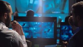 Guardie giurate che guardano le videosorveglianze fotografie stock libere da diritti