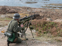 Guarding the Atlantic Wall. A WWII German Soldier (re-enactment) with machine gun guards his section of the Atlantic Wall - Corbiere Point, Jersey. Ammunition Stock Photo