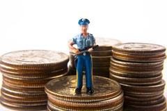 Guarding Money. Miniature policeman on stacks of quarters with dimes and nickels in background Royalty Free Stock Photography