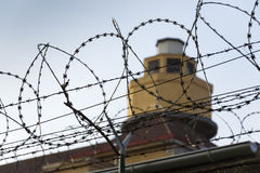 Guarding tower behind barbed wire fence around prison walls Royalty Free Stock Images