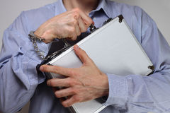 Guarding valuables. Businessman firmly holding a metal briefcase handcuffed to his wrist Royalty Free Stock Photo