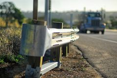 Guardrail on a highway with a large truck approaching. The end piece and termination of a Shiny galvanized guardrail on a black asphalt highway, with a truck in Stock Image