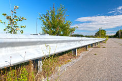 Guardrail next to old road Stock Images