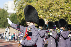 Guards Marching in London during the Changing of the Guards. Soldier leading march near Hyde park in London with arm outstretched wearing white glove and leading stock image