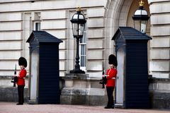 Guards standing at Buckingham Palace. Guards dressed in red uniform and with guns, during the changing of the guards at Buckingham Palace Stock Photos