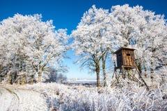 Guarida de madera de la caza delante de los árboles cubiertos por la helada Imagen de archivo