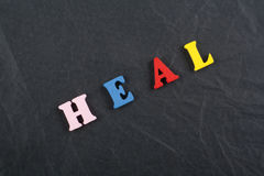 GUARISCA la parola sul fondo nero del bordo composto dalle lettere di legno di ABC del blocchetto variopinto dell'alfabeto, copi  Fotografia Stock Libera da Diritti