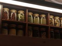 Guarnisca la roba asciutta imballata nello scaffale di legno delle bottiglie di vetro trasparente fotografia stock