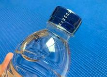 Guarnizione del cappuccio sulla bottiglia di fondo blu immagine stock libera da diritti