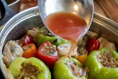 Guarnizione della salsa al pomodoro sui peperoni farciti e sulle foglie del cavolo fotografia stock libera da diritti
