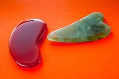 Guasha cykliny dla ciało masażu według antycznej metody strzelali na jaskrawym czerwonym tle fotografia royalty free