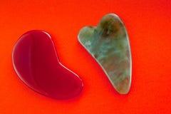 Guasha cykliny dla ciało masażu według antycznej metody strzelali na jaskrawym czerwonym tle obrazy stock
