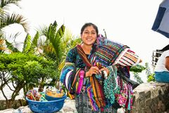 Guatamalian woman salling traditional colorful fabric at the street market in Panajachel, Guatemala. PANAJACHEL, GUATEMALA-DEC 24, 2015: : Guatamalian woman royalty free stock images