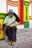 GUATAPE, ANTIOQUIA, COLOMBIA, AUGUST 08, 2018: Old man sitting on the steps of the house. Typically colourful buildings in Guatape. Los Zocalos - the lower parts royalty free stock photo