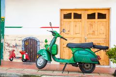Green motorcycle at the colorful town of Guatape, Antioquia. GUATAPE, ANTIOQUIA - COLOMBIA, NOVEMBER 2017. Green motorcycle at the colorful town of Guatape Royalty Free Stock Photos