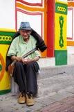 GUATAPE, ANTIOQUIA, COLOMBIE, LE 8 AOÛT 2018 : Vieil homme s'asseyant sur les étapes de la maison Bâtiments en général colorés da photo libre de droits
