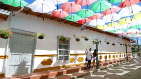 Colored umbrellas suspended on the streets of Guatape Colombia. Guatape April 2018 This is a typical street in Guatape decorated with coloured umbrellas to stock video