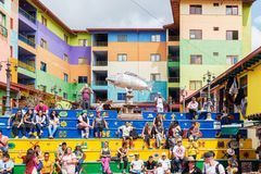 Plaza de Zocalos a popular place to visit in Guatape near Medell. Guatape, Colombia – March 27, 2019: Tourists are sitting on the colourful stairs of Plaza de royalty free stock photo