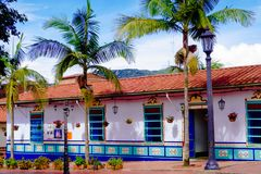 GUATAPE, COLOMBIA - OCTOBER 19, 2017: Beautiful decorated buildings of Guatape city with some palms trees, near Medellin. Antioquia, Colombia stock images
