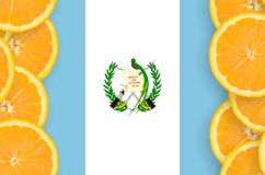 Guatemala flag in citrus fruit slices vertical frame. Guatemala flag in vertical frame of orange citrus fruit slices. Concept of growing as well as import and royalty free stock photo