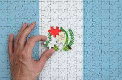 Guatemala flag is depicted on a puzzle, which the man`s hand completes to fold.  stock photo