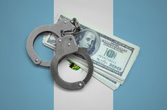 Guatemala flag with handcuffs and a bundle of dollars. Currency corruption in the country. Financial crimes.  stock photography
