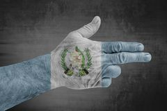 Guatemala flag painted on male hand like a gun. On concrete background royalty free stock images