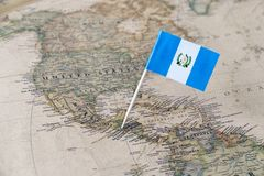 Guatemala flag pin on map. Paper flag pin of Guatemala on a world map showing neighboring countries. Officially the Republic of Guatemala, it is a country stock image