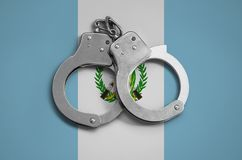 Guatemala flag and police handcuffs. The concept of observance of the law in the country and protection from crime.  royalty free stock image