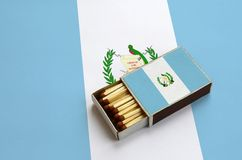Guatemala flag is shown in an open matchbox, which is filled with matches and lies on a large flag.  royalty free stock photos