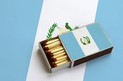Guatemala flag is shown in an open matchbox, which is filled with matches and lies on a large flag.  stock images
