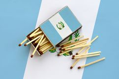Guatemala flag is shown on an open matchbox, from which several matches fall and lies on a large flag.  royalty free stock image