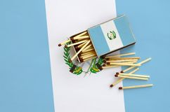 Guatemala flag is shown on an open matchbox, from which several matches fall and lies on a large flag.  stock photo