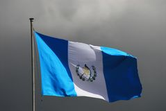Guatemala- Flag Waving Against a Dark Sky. Guatemala is working hard to evolve into the modern era. Perhaps this flag is a metaphor stock image
