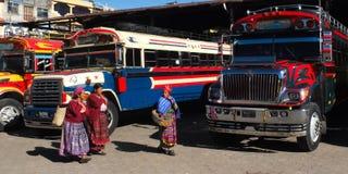 Guatemalaanse vrouwen dichtbij gekleurde bussen. stock foto